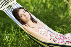 Young woman in cocktail dress relaxing in a hammock. Royalty Free Stock Photo