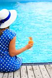 Young woman with cocktail glass near swimming pool Stock Images