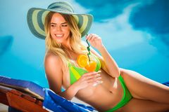 Young woman with cocktail glass near swimming pool on a deck chair. Portrait of young woman with cocktail glass chilling in the tropical sun near swimming pool stock photo