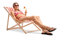 Young woman with a cocktail relaxing in a deck chair Stock Photos
