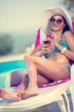 Young woman with cocktails relaxing in sunbed Royalty Free Stock Images