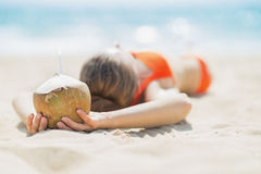 Young woman with coconut relaxing on beach Royalty Free Stock Images
