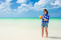 Young woman with coconut on tropical white beach Stock Photography