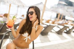 Young woman with coctail on the beach Stock Photos
