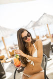 Young woman with coctail on the beach Royalty Free Stock Photos