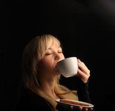Young  woman with coffe  on a dark background Royalty Free Stock Image