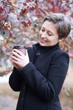 Young woman with coffee in city park, autumn season, red leaves royalty free stock photography