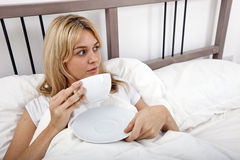 Young woman with coffee cup looking away in bed Royalty Free Stock Images