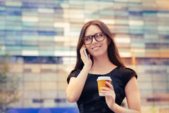 Young Woman with Coffee Cup on the Phone Out in the City Royalty Free Stock Photos