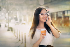 Young Woman with Coffee Cup on the Phone Out in the City Stock Photography