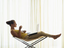 Young woman with coffee cup using laptop at home Stock Photo