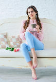 Young woman with coffee and flowers on a sofa. Beautiful young woman with stylish braids hairstyle enjoying a cup of her morning coffee with comfort on a sofa Royalty Free Stock Photography