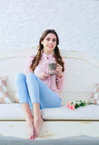 Young woman with coffee and flowers on a sofa. Beautiful young woman with stylish braids hairstyle enjoying a cup of her morning coffee with comfort on a sofa Stock Photography