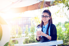 Young woman with coffee in garden. Real time in light nature Royalty Free Stock Photography