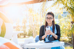 Young woman with coffee in garden. Real time shot in light nature Royalty Free Stock Photography