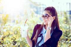 Young woman with coffee in garden. Real time shot in light nature Royalty Free Stock Image