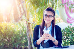 Young woman with coffee in garden. Take photo in light nature Royalty Free Stock Photos