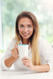 Young woman with coffee in kitchen Stock Image