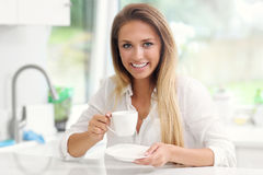 Young woman with coffee in kitchen Stock Images