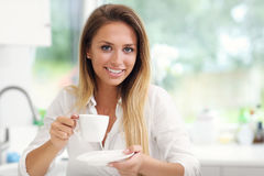Young woman with coffee in kitchen Stock Photography