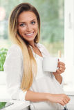 Young woman with coffee in kitchen Stock Photo