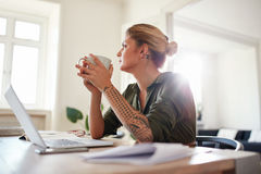 Young woman with coffee looking away and thinking Royalty Free Stock Photo