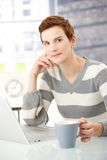 Young woman with coffee mug and laptop Royalty Free Stock Photo