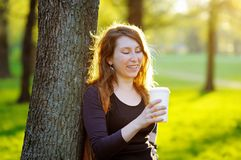 Young woman with coffee outdoors Royalty Free Stock Photography