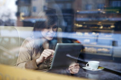 Young woman in coffee shop. Young woman using tablet in coffee shop Stock Photo
