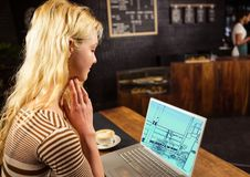 Young woman in coffee shop with laptop, on the screen the draw of the new design to the office (two- Royalty Free Stock Image