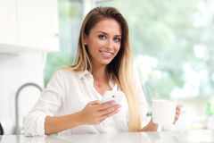 Young woman with coffee and smartphone in kitchen Stock Images