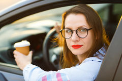 Young woman with coffee to go driving her car Stock Photos