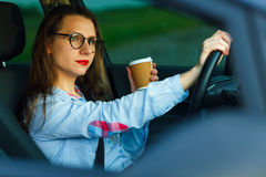 Young woman with coffee to go driving her car Stock Photography