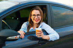 Young woman with coffee to go driving her car Royalty Free Stock Photo