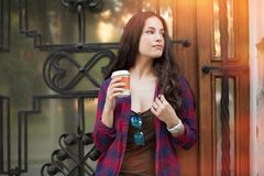 Young woman with  coffee to go outdoor in city Royalty Free Stock Photos