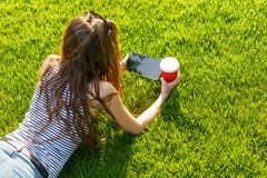 Young woman with a coffee to go and tablet on a lawn Stock Photos