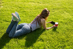 Young woman with a coffee to go and tablet on a lawn Royalty Free Stock Images