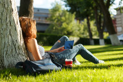 Young woman with a coffee to go and tablet on a lawn Stock Photo