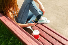 Young woman with a coffee to go and tablet pc on a bench Stock Photography