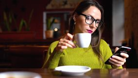Young woman with coffee using smartphone in cafe. Young, happy woman with coffee using smartphone in cafe stock footage