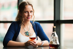 Young woman with a cognac at restaurant Stock Photos