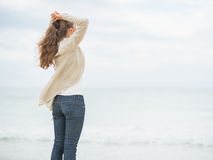 Young woman on cold beach looking into distance Stock Photo