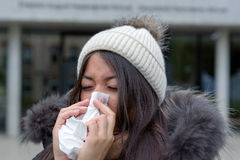 Young woman with a cold blowing her nose. Young woman with a seasonal winter cold or flu wearing a furry jacket and knitted cap blowing her nose on a white Stock Photo