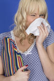 Young Woman with Cold Flu Blowing Nose Holding a Hot Water Bottle Stock Images