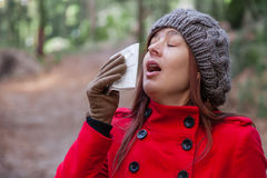 Young woman with a cold or flu sneezing Stock Photo