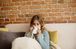 Young woman with cold, flue. Young ill woman sitting on sofa, she is having cold or flu Royalty Free Stock Photos