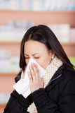 Young woman with a cold using paper tissue Stock Photo