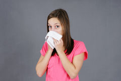 Young woman with colf or flu. Young woman blowing her nose in a tissue, sick from a cold or flu virus, could be sad or depressed, great for health issues Stock Photo