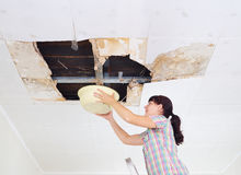 Young Woman Collecting Water In basin From Ceiling. Ceiling pane Royalty Free Stock Images