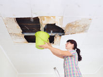 Young Woman Collecting Water In Bucket From Ceiling. Ceiling pan Royalty Free Stock Images
